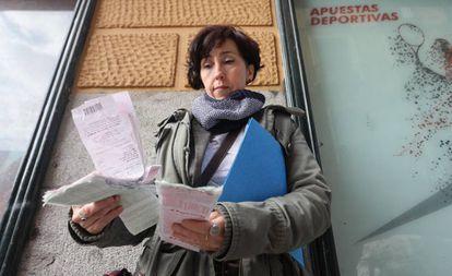 Susana Fonseca, madre de un hijo ludópata desde hace 10 años posando con las últimas apuestas de su hijo en un local de Lavapiés.