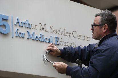 Un operario quita el nombre del mecenas  Arthur M. Sackler de la entrada a la Tufts School of Medicine de Boston en diciembre de 2019.