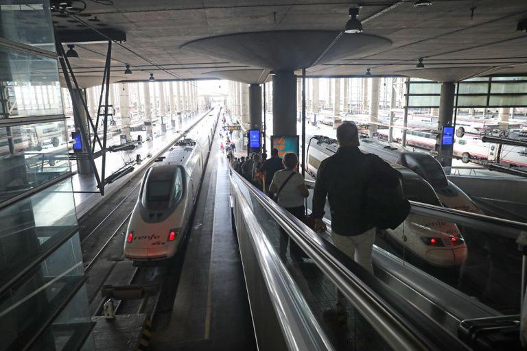 Varios pasajeros acceden al andén por una cinta mecánica en la estación Madrid-Puerta de Atocha.
