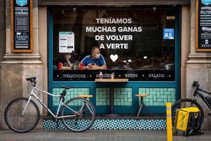 Una pareja de turistas en un bar de Barcelona hoy domingo, durante el primer día sin toque de queda en Cataluña.