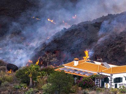 La lava del volcán de La Palma cerca de una vivienda este martes.