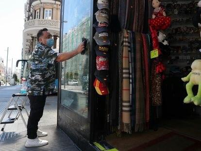Un trabajador limpia el escaparate de una tienda del centro de Madrid.
