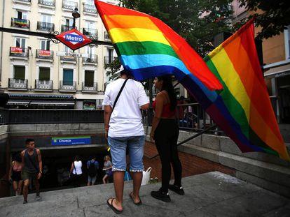 Dos jóvenes con banderas arcoiris en la estación de metro de Chueca.