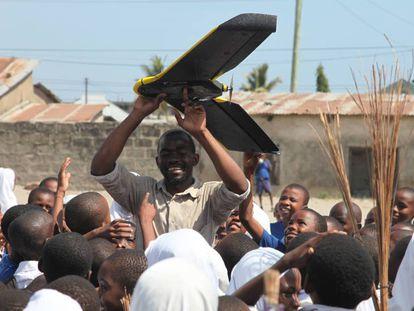 Escolares del distrito de Tandale en Dar es Salaam (Tanzania), observan una pequeña aeronave no pilotada o dron.