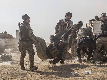 Soldados iraquíes transportan a un herido cerca de Mosul.