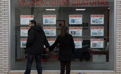 Dos personas miran el escaparate de una inmobiliaria en Madrid.