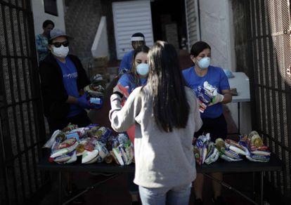 Activistas ofrecen alimentos a personas de escasos recursos en San José, en medio de la contingencia por la Covid-19.