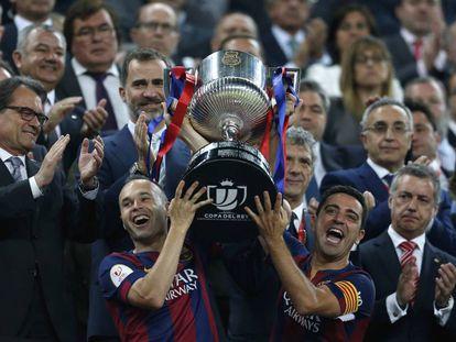 Iniesta y Xavi levantan la Copa de 2015.