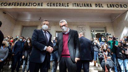 El primer ministro de Italia, Mario Draghi (izquierda), saluda este lunes al secretario general de CGIL, Maurizio Landini, frente a la sede en Roma del sindicato atacado este fin de semana por grupos fascistas.