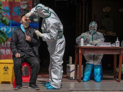 Un trabajador sanitario toma muestras a un hombre en la calle
