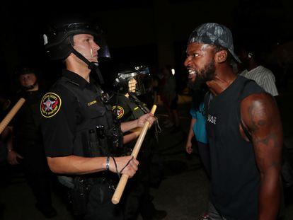 Un hombre enfrenta a un policía, en las protestas en Kenosha, Wisconsin.