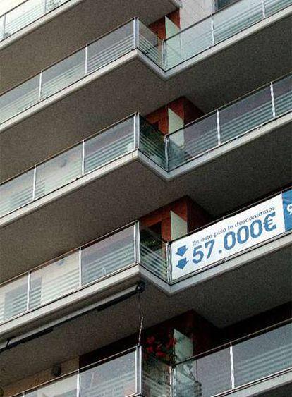 Una promoción de viviendas luciendo carteles de rebajas.
