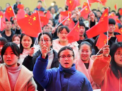 Varios estudiantes de una universidad de la provincia de Anhui ondean banderas de China, en 2018.