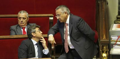 El concejal de Seguridad Ciudadana, Miquel Domínguez (de pie), habla con el de Juventud, Cristóbal Grau, durante el pleno de Valencia.