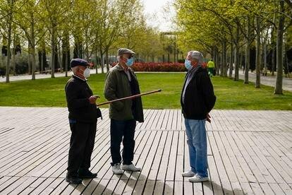 Tres personas conversan a finales de marzo en el Parque Lineal del Manzanares en Madrid.