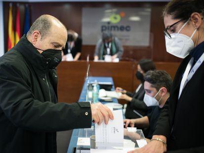 Un hombre vota durante la jornada electoral en la patronal Pimec.