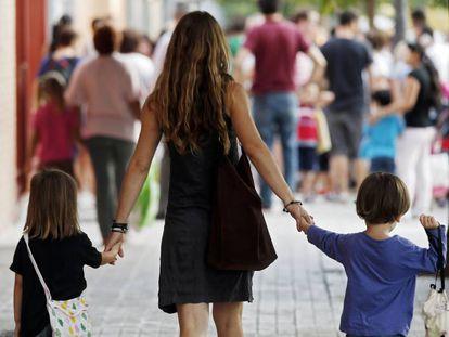 Una madre lleva a sus hijos al colegio.