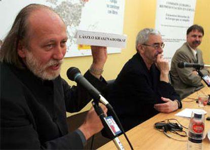 El escritor húngaro László Krasznahorkai muestra un cartel con su nombre junto al autor de origen rumano Adan Bodor y el traductor Adan Kovacsis.