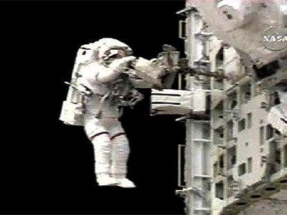 Piers Sellers, con rayas rojas en las perneras del traje como distintivo, durante el paseo espacial de ayer.