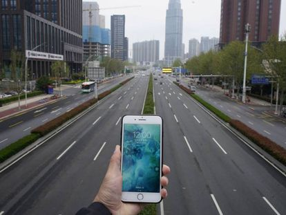Una persona sostene un teléfono móvil frente a una carretera casi vacía en Wuhan.