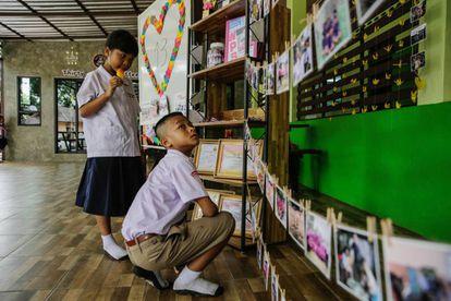 Compañeros de uno de los niños atrapados en la cueva de Tham Luang (Tailandia) le rinden tributo a la entrada de su escuela este lunes.