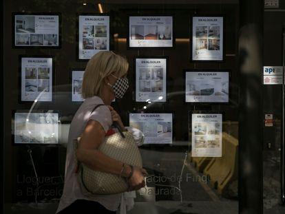 Una mujer pasa delante una inmobiliaria de alquiler de viviendas en Barcelona.