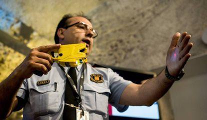 Un intendente presenta la pistola modelo Taser X2 que usarán los Mossos