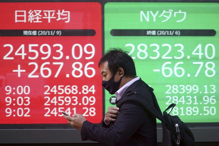 Un hombre pasa junto a un panel de precios en Tokio el lunes.
