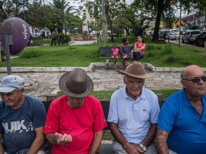 Cuatro hombres descansan en la plaza central de Eldorado delante de dos mujeres y una niña.