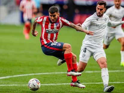 Correa trata de zafarse de Pulido durante el Atlético-Huesca (2-0) disputado este jueves en el Wanda Metropolitano. (AP Photo/Manu Fernandez)