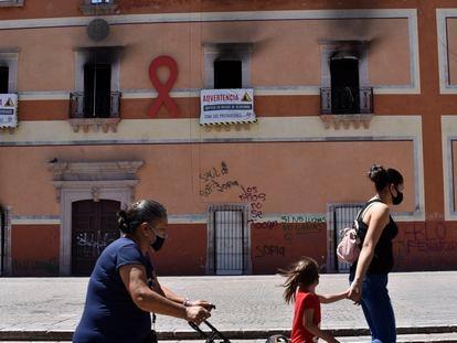 Tres mujeres caminan frente al Palacio Municipal de Fresnillo, Zacatecas, quemado tras una protesta por el feminicidio de una menor.