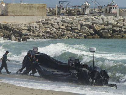 Guardias civiles empujan una lancha semirrígida utilizada por los narcos en el Estrecho.