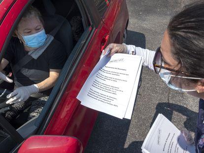 Una representante del Ayuntamiento de Hialeah, Florida, reparte documentos para solicitar los beneficios por desempleo.