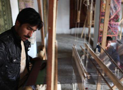 Mohamed Munir teje un pañuelo en la tienda de su tío.