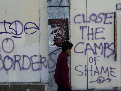 Un niño pasa delante de unas pintadas hechas en Atenas a mediados de abril durante una manifestación contra la guerra en Siria y la actitud de la UE hacia los refugiados.