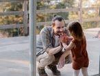 Un padre saluda cariñosamente a su hija.