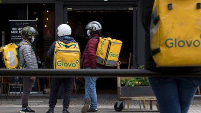 Unos 'riders' esperan para entregar su pedido en la zona de Azca de Madrid, este miércoles.