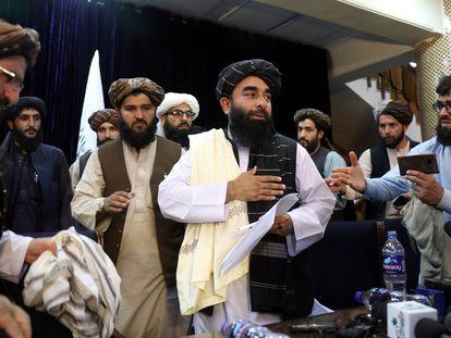 Zabihullah Mujahid (centro), portavoz de la insurgencia afgana, interviene en la primera rueda de prensa de los talibanes tras hacerse con el poder, celebrada este martes en Kabul.