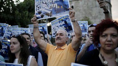 Manifestantes griegos, en una protesta este lunes en Atenas, con pancartas en las que se puede leer 'Nos quedamos en Europa'
