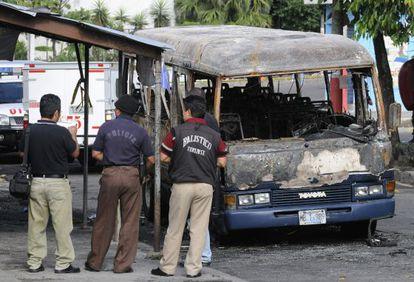 Agentes de policía del El Salvador observan los restos de un autobús en el que fueron hallados 14 cuerpos calcinados en 2010.