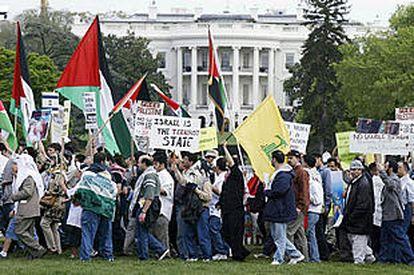 Un grupo de manifestantes  pasa por delante de la  Casa Blanca enarbolando banderas palestinas y pancartas contra Israel.