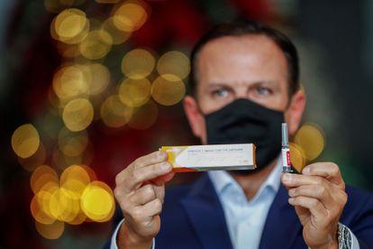 El Gobernador de São Paulo, Joao Doria, muestra una caja y una ampolleta de Coronavac durante una rueda de prensa celebrada el 7 de diciembre.