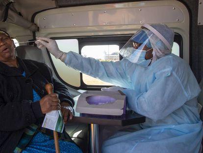 Un sanitario hace una PCR a una mujer en una unidad móvil en Johanesburgo (Sudáfrica).