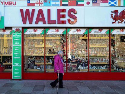Una mujer con pantalla facial protectora camina por el centro de Cardiff, en Gales.