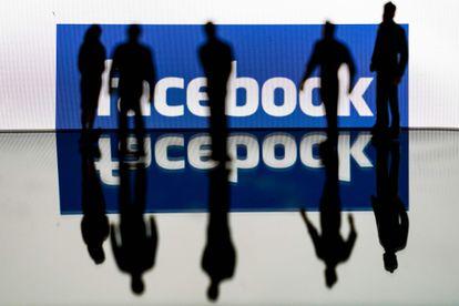 Varias personas ante un logo de Facebook, en febrero pasado.