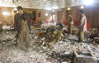 Tres milicianos contemplan los destrozos en la sede de la Unión Patriótica del Kurdistán, ayer en Erbil.