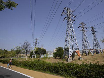 Una persona pasa cerca de varias torres eléctricas, en Madrid.