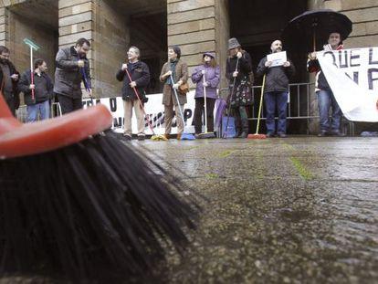 """Manifestación del BNG ante el Ayuntamiento de Santiago, con escobas y fregonas para reclamar """"limpieza""""."""