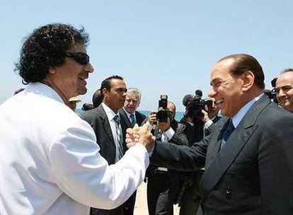 El líder libio, Muammar el Gaddafi, saluda a Silvio Berlusconi en el puerto de Sirta ayer al inicio de la visita oficial del primer ministro italiano.