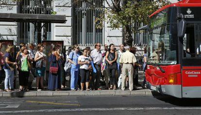Fila en una parada de autobús en Valencia.